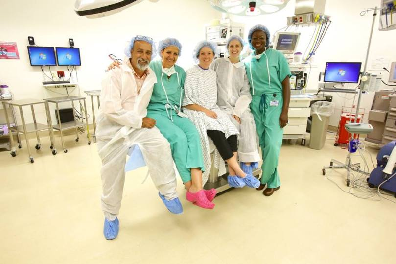 Five people pose in an operating room